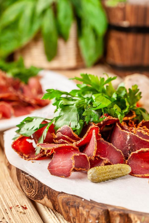 Concept of Georgian restaurant. Beer snack on wooden table,, dried sausage, basturma, smoked meat and parsley with dill royalty free stock image