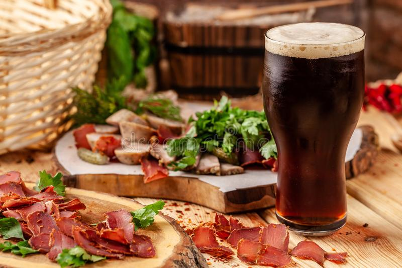 Concept of Georgian restaurant. Glass of black beer with foam stands on wooden table with beer snack. Concept of Georgian restaurant. A glass of black beer with royalty free stock images