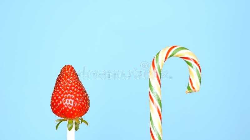 Concept gezond en ongezond voedsel aardbei tegen suikergoed op een heldere blauwe achtergrond royalty-vrije stock fotografie