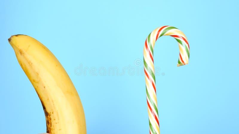 Concept gezond en ongezond voedsel banaan tegen suikergoed op een heldere blauwe achtergrond stock afbeelding