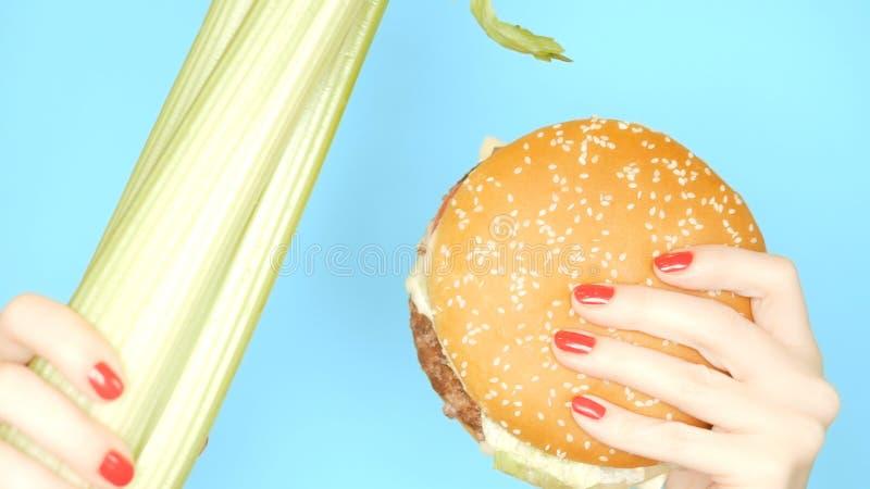 Concept gezond en ongezond voedsel selderiestelen tegen hamburgers op een heldere blauwe achtergrond vrouwelijke handen met stock foto's