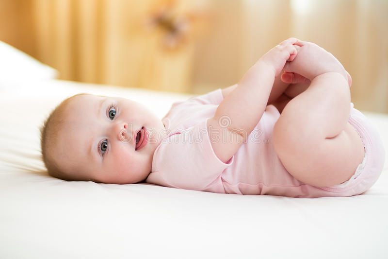 Concept gezond kind Leuke baby die op haar terug op bed in ruimte liggen, die benen met haar handen houden stock fotografie