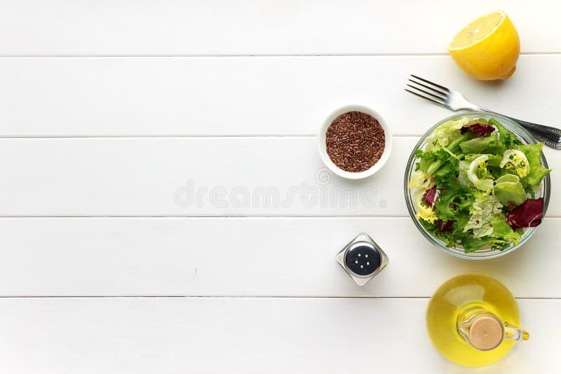 Concept gezond voedsel Verse salade in kom met lijnzaad op witte houten lijst stock foto