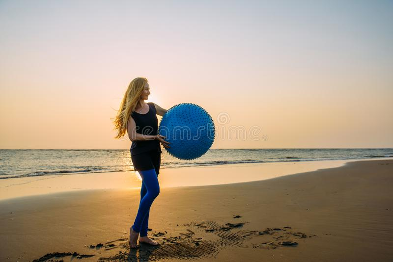 Concept gezonde levensstijl voor vrouwen Glimlachend jong wijfje met lang blondehaar met grote blauwe bal stock afbeelding