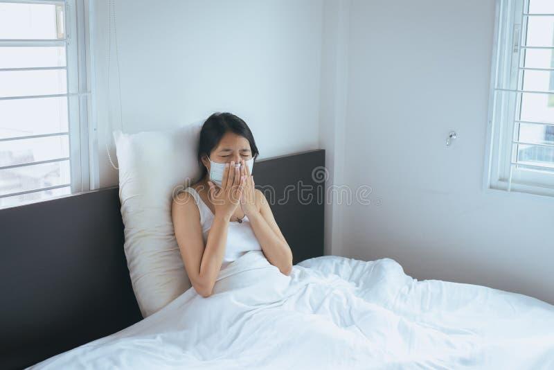 Concept gezondheidsvrouw die beschermend masker met koude het blazen en lopende neus op bed, het zieke vrouw niezen gebruiken royalty-vrije stock afbeelding