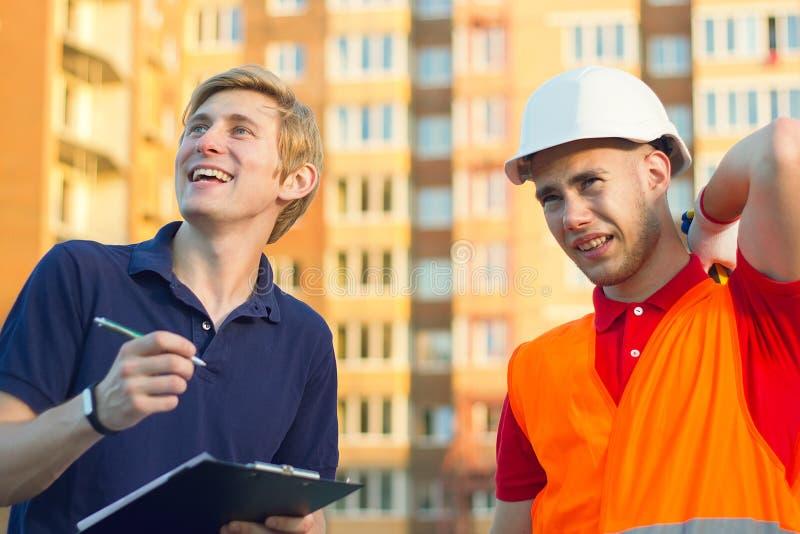 Concept, glimlachende groep bouwers in bouwvakkers met klembord stock afbeeldingen