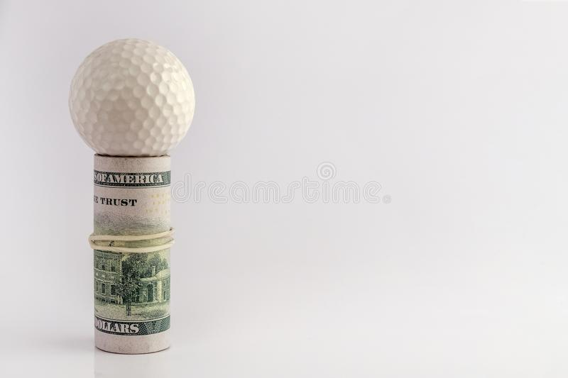 Concept of golfer competitions for money, financial risk, corruption, or sports betting. Golf ball on top of a roll of US hundred royalty free stock images