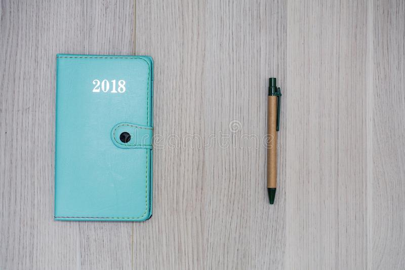 Green note book with pen. Concept green note book 2018 year with pen on wooden floor stock images
