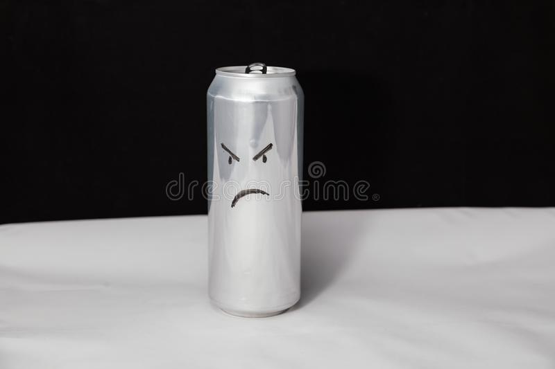 The concept of grumpy man. Angry emoticon on aluminium can, Emoji with rageful face. On black background stock images