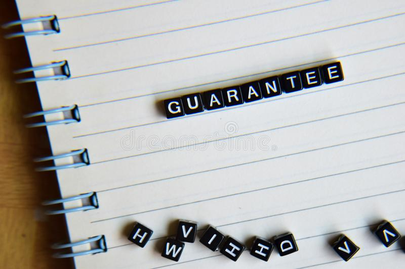 Concept of Guarantee word on wooden cubes with books in background royalty free stock images