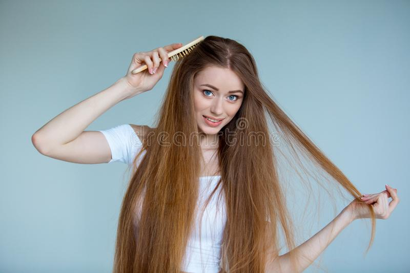 Concept of hair loss. Close up portrait of unhappy sad stressed young woman with long dry brown hair, isolated on grey royalty free stock image