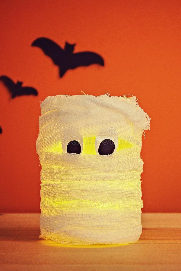 The concept for Halloween. Bats and mummy from jar, bandages and candles on an orange background stock photo