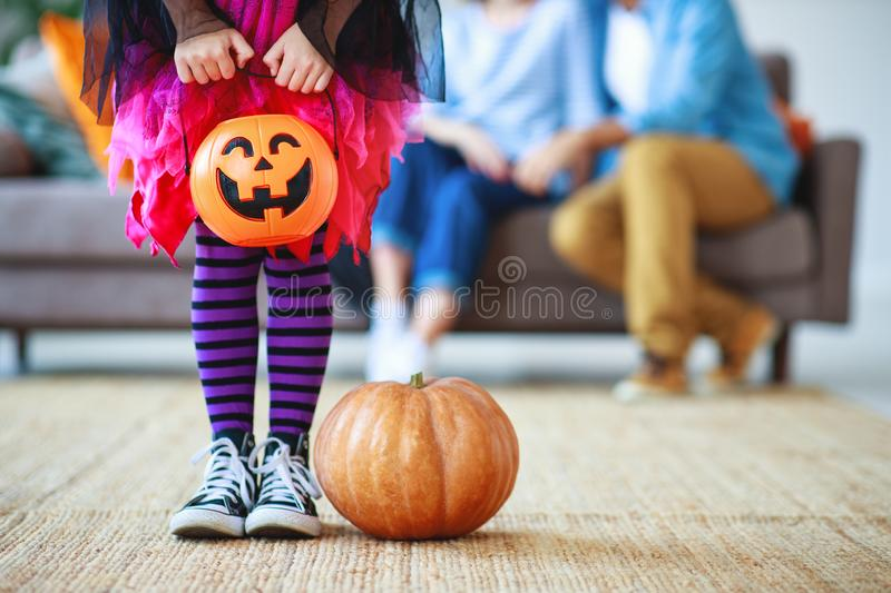 Concept of Halloween. child girl legs in witch costume with pumpkin royalty free stock photos