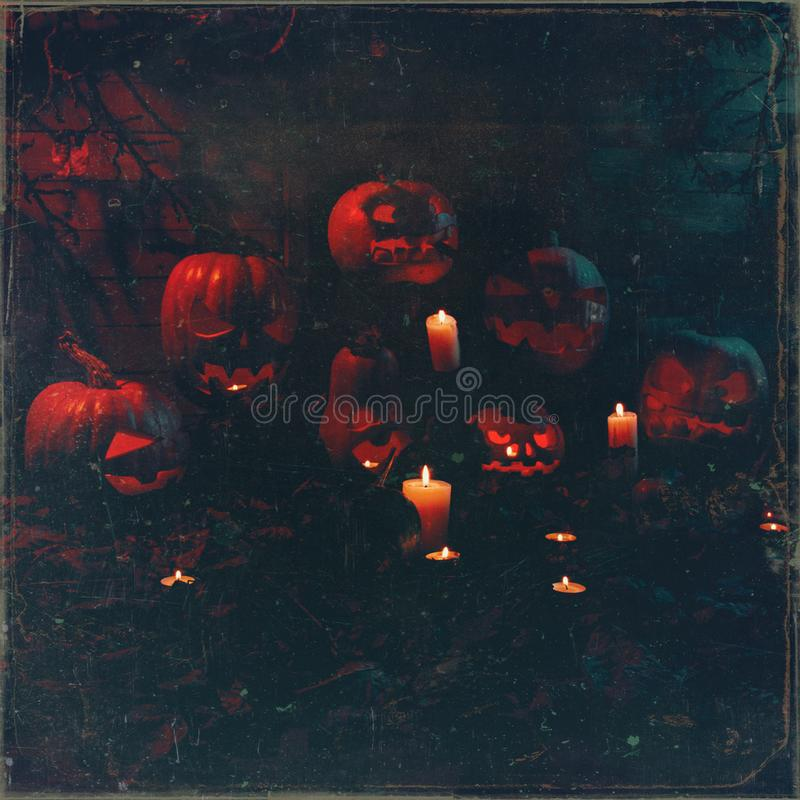 Concept of Halloween. many glowing orange and blue light angry terrible pumpkin, leaves, jack-lamp with candle of a happy. Halloween, on a wooden background stock photography