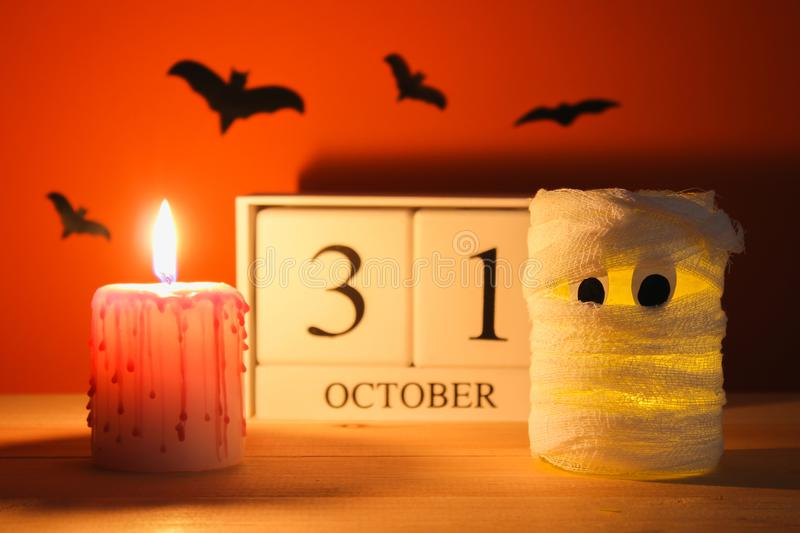 The concept for Halloween. Mummy from a can, gauze and candles, a wooden calendar showing October 31. The concept for Halloween. Mummy from a can, gauze and stock photos