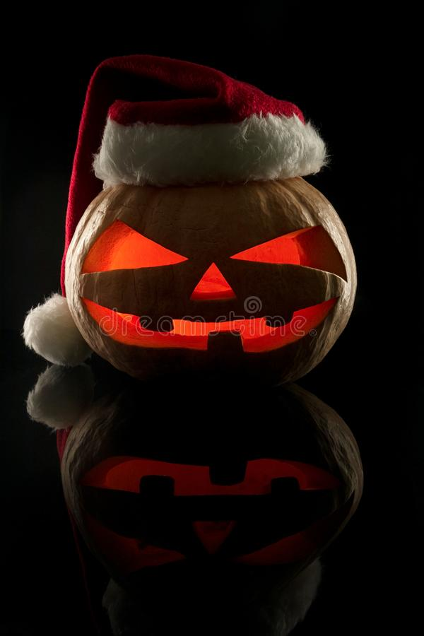 The concept of Halloween and the New Year and Christmas. The evil scary pumpkin Santa in the Santa Claus hat in the dark with ref stock photos