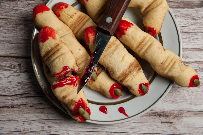Terrible and delicious cookies `witch`s finger`, a knife in the blood in a plate on a wooden background. stock image