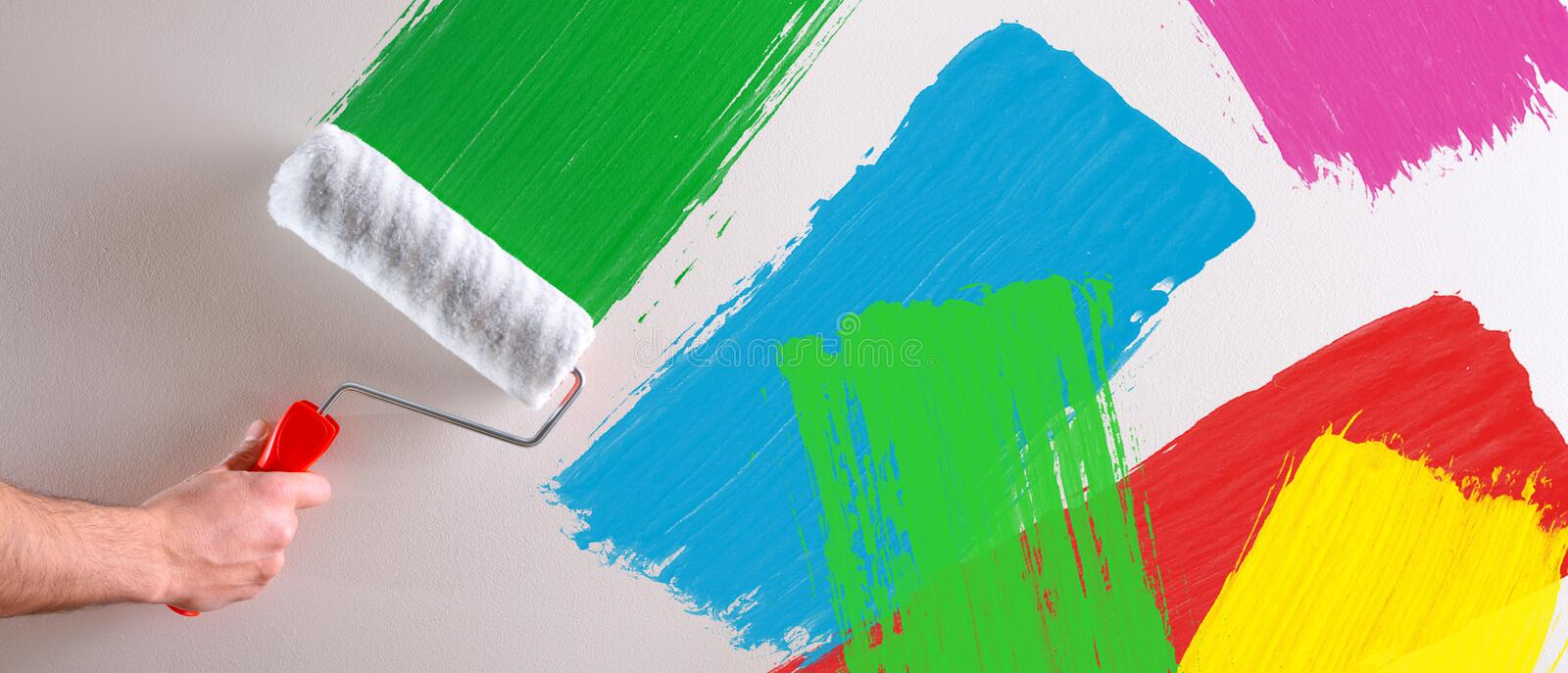 Concept of hand painting multicolored samples on wall stock photo