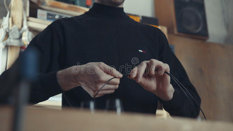 The concept of handmade crafting style. Close-up of wire in male hands stock photo