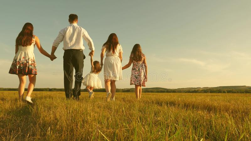 Concept of a happy childhood. mother, father and little daughter with sisters walking in field in the sun. Happy young royalty free stock images