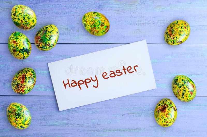 Concept Happy easter. Painted eggs and white otkrka with the inscription. stock photos