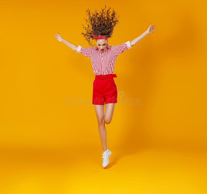 Concept happy emotional young woman in red  jumping   on yellow background stock photo