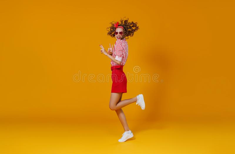 Concept happy emotional young woman in red  jumping   on yellow background royalty free stock photography