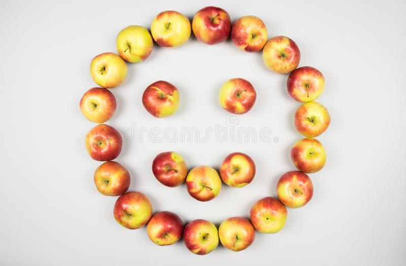 Concept of happy and healthy life as red and yellow fresh apples forming smiling face on white background. stock photography