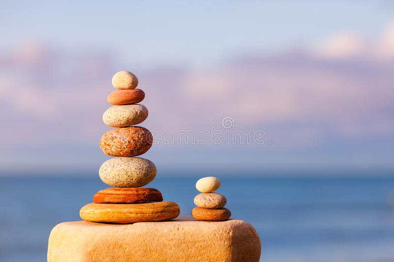 Concept of harmony and balance. Evening calm. Pyramid of colorful, balanced stones on the sea background. beautiful evening light. Concept of harmony and balance stock photography