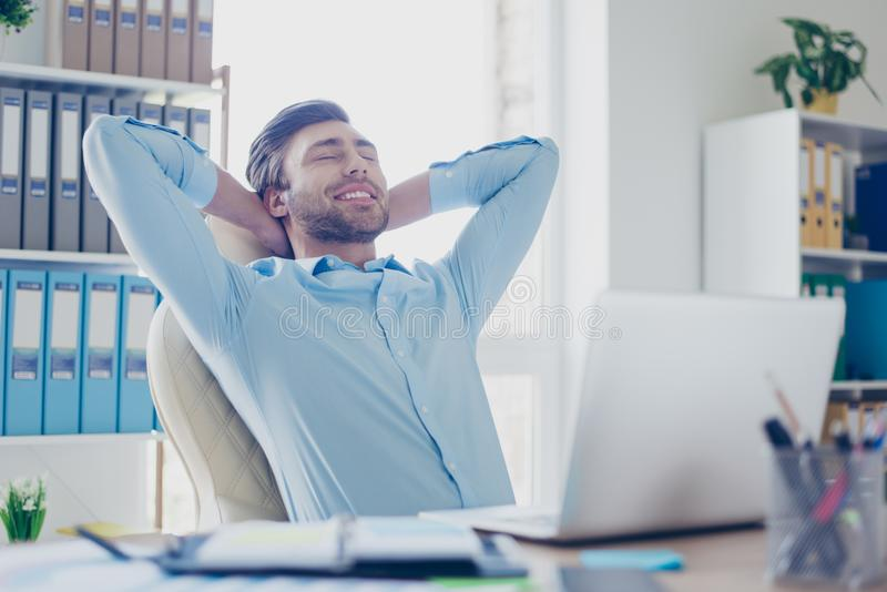 Concept of having perfect and lovable work or having break at workstation. Cheerful and delightful smiling young employee is royalty free stock image