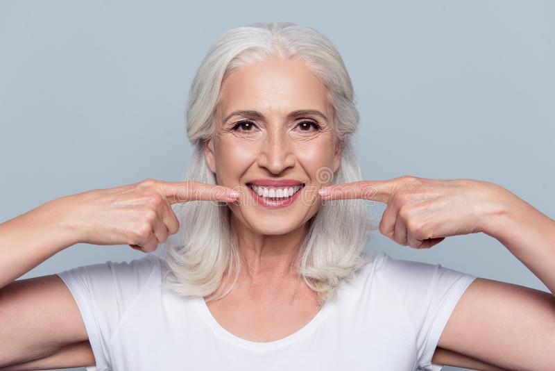 Concept of having strong healthy straight white teeth at old age. Close up portrait of happy with beaming smile female pensioner pointing on her perfect clear stock images