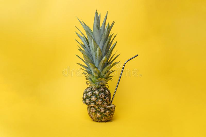 Concept of health and environment with a ananas, pineapple cut in half shot against a yellow background with a metal straw in it. Concept of health and healthy stock image