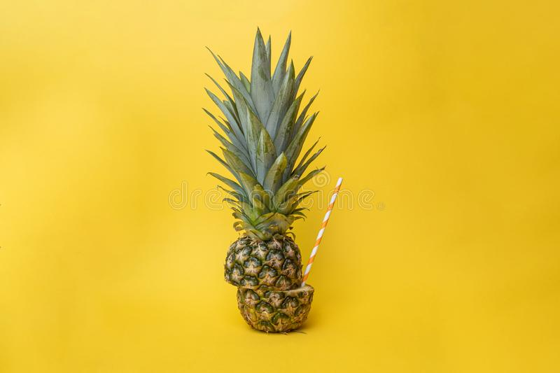 Concept of health with a ananas, pineapple cut in half shot against a yellow background with a orange paper straw in it. Concept of health and healthy eating stock image