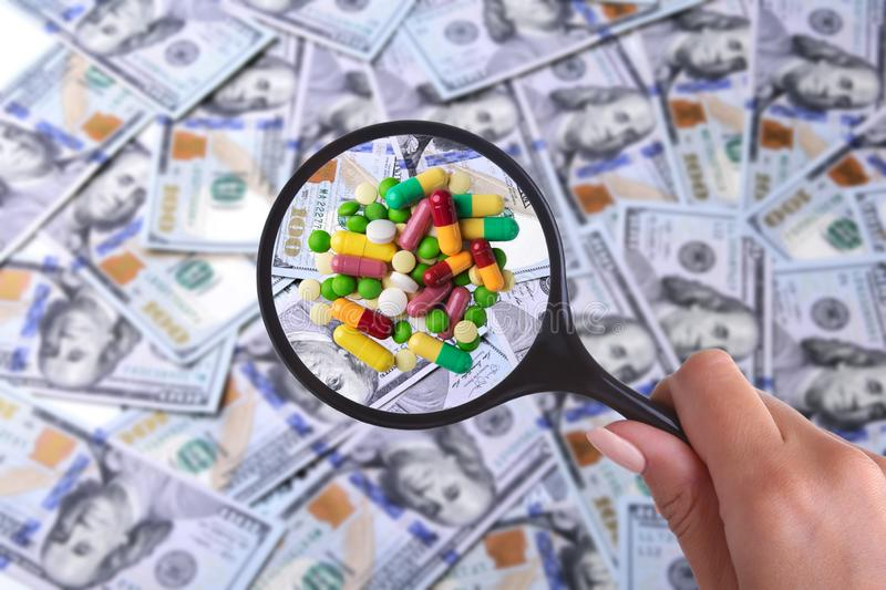 Concept of Health insurance. Assortment pills in magnifier against the background of Many dollar banknotes.  stock photo