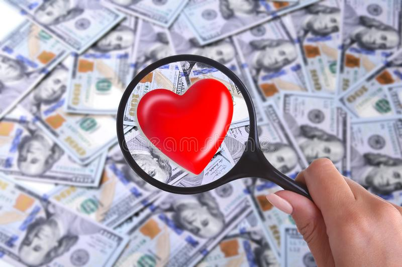 Concept of Health insurance. Red heart in magnifier against the background of Many dollar banknotes.  royalty free stock images