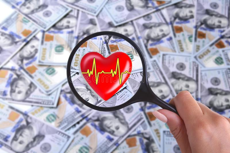 Concept of Health insurance. Red heart in magnifier against the background of Many dollar banknotes.  royalty free stock photo
