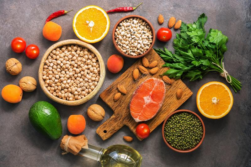Concept healthy balanced food, salmon,legumes, fruits, vegetables, olive oil and nuts, dark rustic background. Flat lay, top view royalty free stock photography