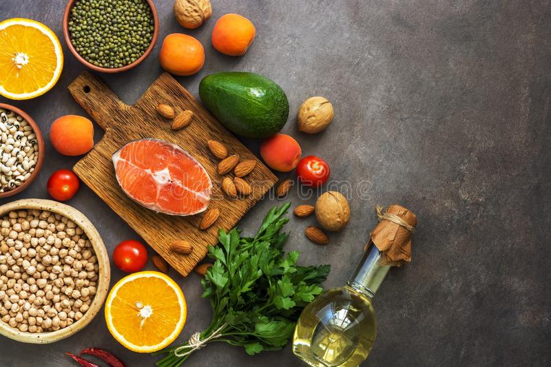 The concept of a healthy balanced meal, salmon,legumes, fruits, vegetables, olive oil and nuts, dark rustic background. Top view, royalty free stock photos