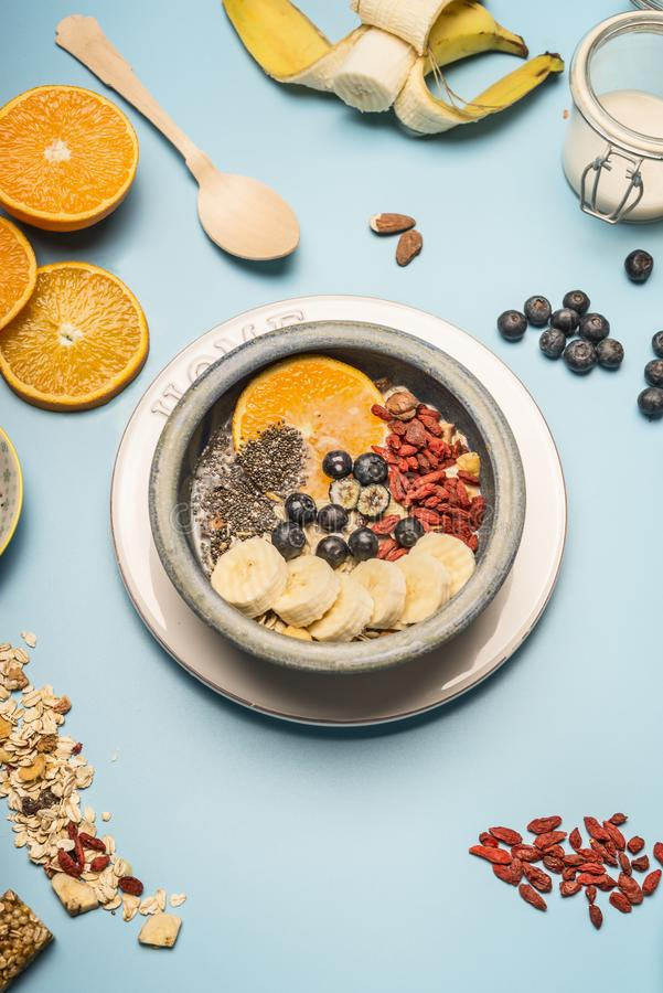 Concept of a healthy breakfast, berries, bananas, oranges, cereals, and milk in a vintage bowl on a blue background, space for tex. Concept of a healthy royalty free stock image