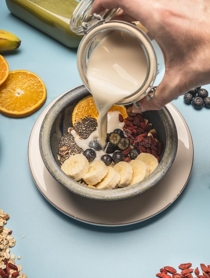Concept of a healthy breakfast, berries, bananas, oranges, cereals, and milk in a vintage bowl on a blue background, space for tex. Concept of healthy breakfast royalty free stock images
