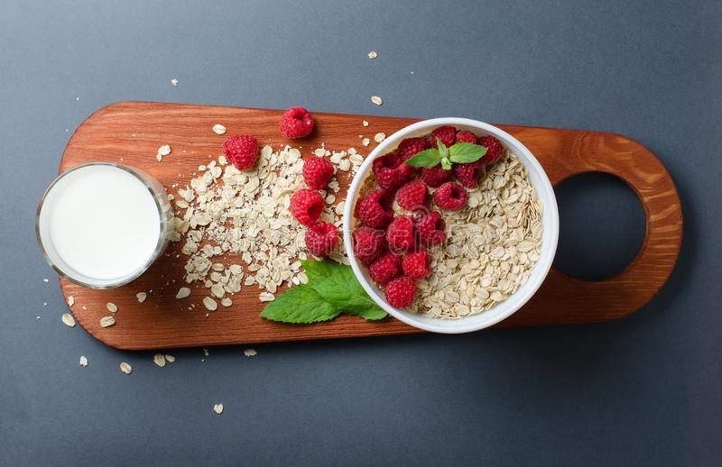 The concept of a healthy diet. Oatmeal, raspberry, milk, mint leaves on a dark cutting Board. Flat Lay stock photography