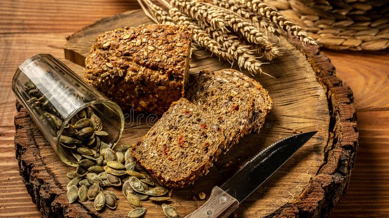 The concept of healthy eating. Whole grain bread with seeds of goji berry, pumpkin, on a plate on a wooden background stock photography