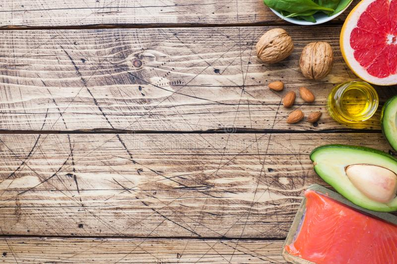 Concept Healthy food antioxidant products: fish and avocado, nuts and fish oil, grapefruit on wooden background. Copy space. Concept Healthy food antioxidant royalty free stock images