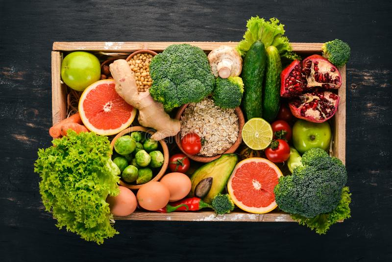 The concept of healthy food. Fresh vegetables, nuts and fruits in a wooden box. On a wooden background. royalty free stock photos