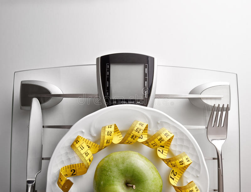 Concept healthy food on table with apple close up. Cutlery with yellow tape measure and green apple on a scale plate on a white table. Concept of healthy eating stock images