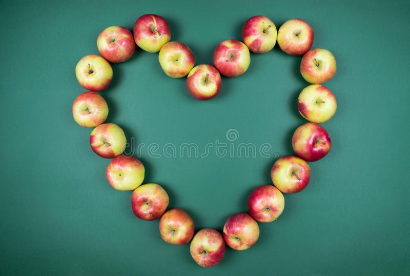 Concept of healthy fruit apples forming shape of hearth on green background. royalty free stock photos