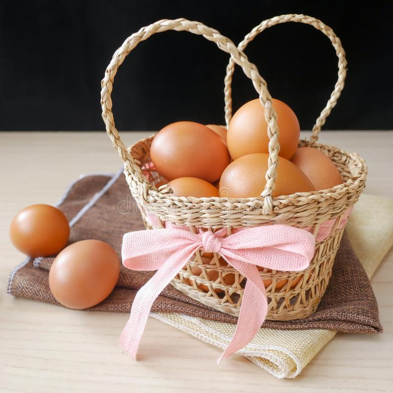 Concept healthy gift, Fresh brown chicken eggs in basket gift set on wooden table royalty free stock images