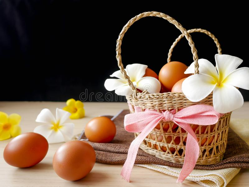 Concept healthy and happiness, Fresh brown chicken eggs in basket gift set decorated with white flowers on wooden table stock photography