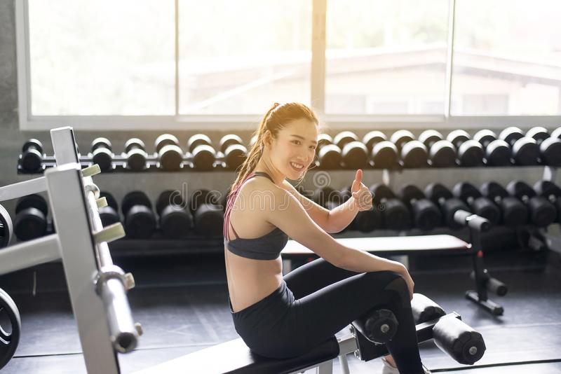 Concept healthy and lifestyle,Fit asian woman showing thumbs up and relax after the training session in gym,Women taking a break a. Fter exercise and workout stock photos