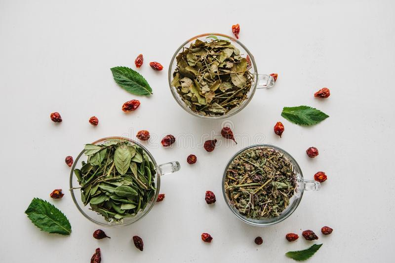 The concept of a healthy lifestyle. Many different ingredients for making herbal tea inside the mugs stock images
